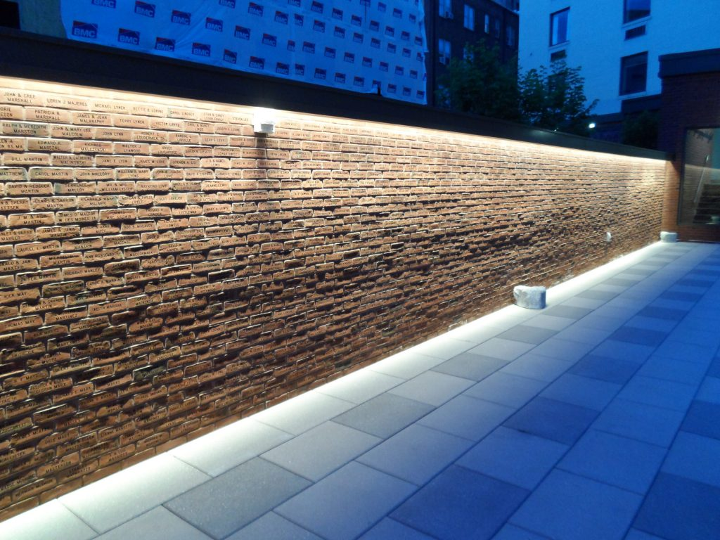 Wall of engraved donor recognition bricks at night.